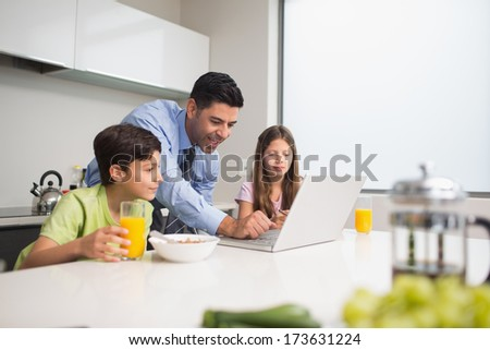 Father using laptop while young kids having breakfast in the kitchen at home - stock photo
