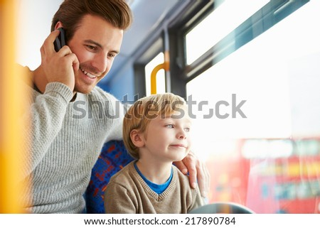 Father Using Mobile Phone On Bus Journey With Son - stock photo