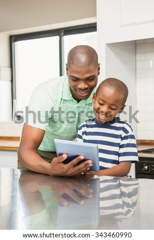 Father using tablet with his son in the kitchen