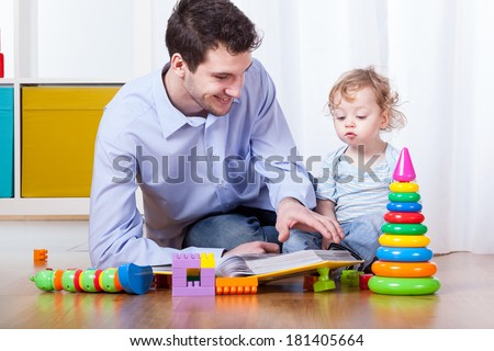 Father viewing family photo album with son - stock photo