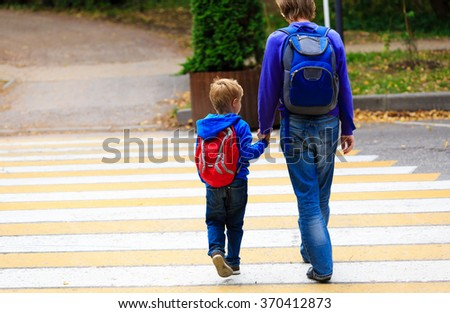 father walking little son to school or daycare