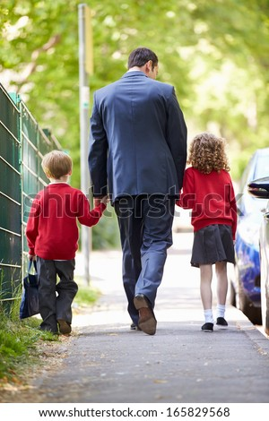Father Walking To School With Children On Way To Work - stock photo