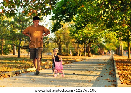 father walking with his baby girl in the park - stock photo