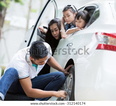 Father was to change the tire because the tire was leaking park beside the mother and children cheering - stock photo