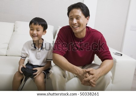 Father watching son play video game on couch, front view