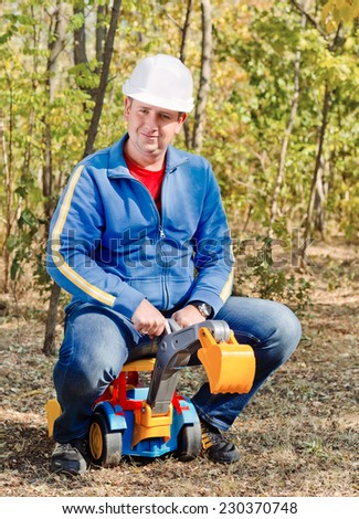 Father wearing a hardhat riding on his kids colorful plastic toy excavator outdoors in the garden looking at the camera with a smile - stock photo