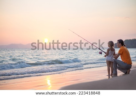 Father with adorable daughter fishing with rod on ocean beach on sunset - stock photo