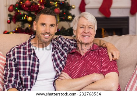 Father with arm around grandfather posing on sofa at home in the living room - stock photo