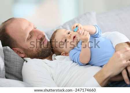 Father with baby boy relaxing in sofa at home - stock photo