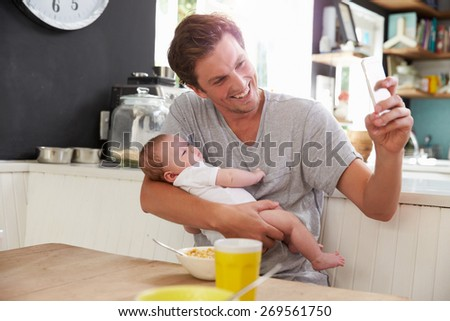 Father With Baby Daughter Taking Selfie On Mobile Phone - stock photo