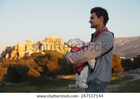 Father with baby near fire sunset Acropolis in Athens,Greece. - stock photo