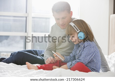 Father with boy listening music on headphones in bedroom - stock photo