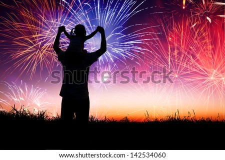 father with child standing on the hill and watching the fireworks - stock photo