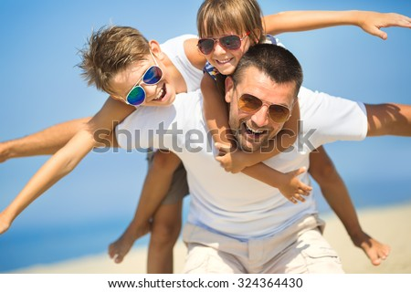 Father with children having fun on the beach at the day time. - stock photo