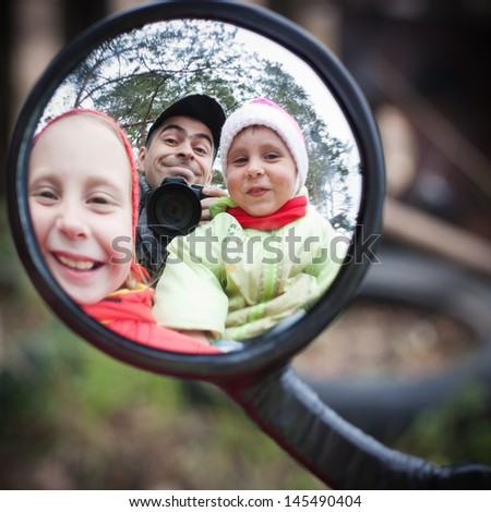 Father with children looking at the a distorting mirror. - stock photo