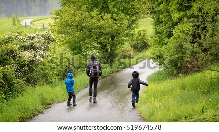 Father with children walking on countryside road on rainy day