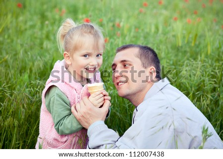 Father with daughter eating ice-cream outdoor - stock photo