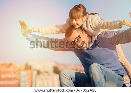 Father with daughter having fun  at the day time. - stock photo