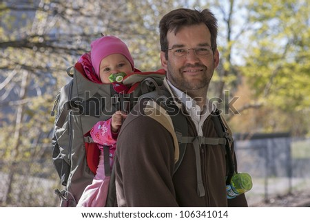 Father with daughter in backpack carrier - stock photo