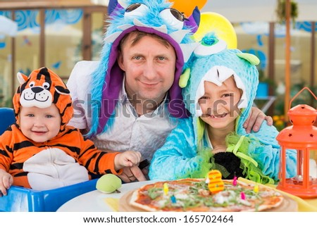 Father with daughter in monster costumes and baby boy in tiger costume celebrate the birthday in a cafe - stock photo