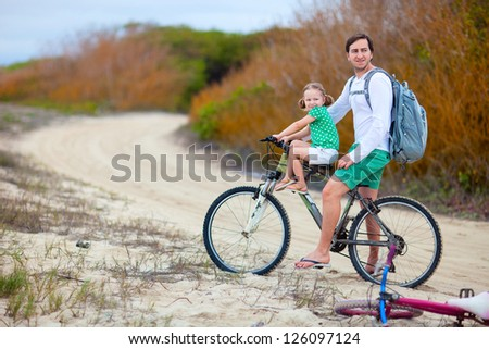 Father with daughter riding a bike along a coast