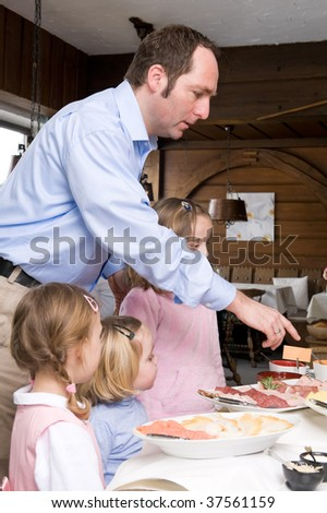 Father with daughters at  breakfast  buffet in a small hotel - stock photo