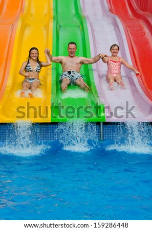 Father with daughters on tropical slide - stock photo