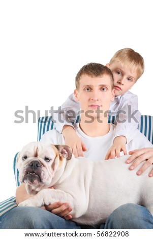 father with english bulldog is sitting on a chair. his son is standing behind him.