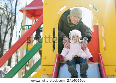Father with her baby girl having fun on the playground - stock photo