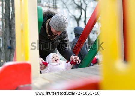 Father with her baby girl having fun on the playground