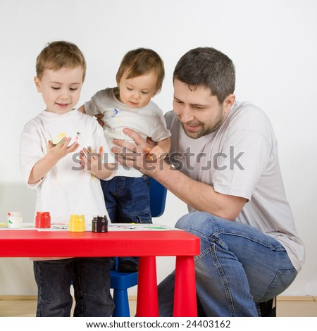 Father with his childern enjoy painting with assorted colours