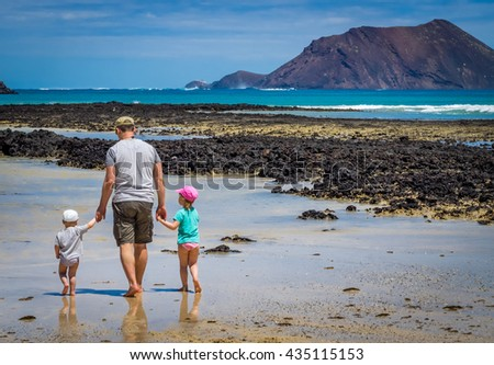Father with his children, little boy and girl, walking in water waiting for wave to come on the beach in summer