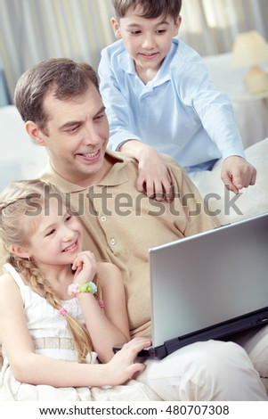 Father with his children using laptop at home
