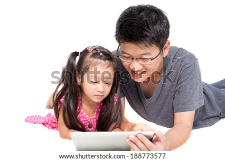 Father with his daugher playing tablet pc