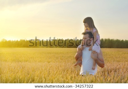 Father with his daughter in wheat field - stock photo