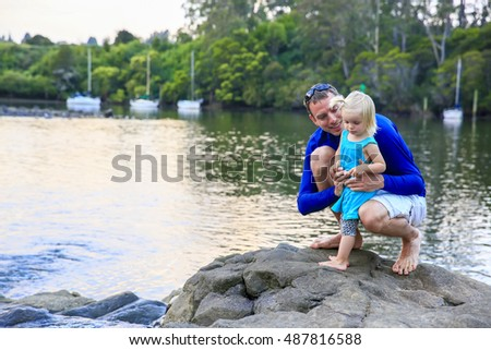 Father with his daughter relaxing, having fun on the rocky coastline of Kerikeri river, New Zealand.