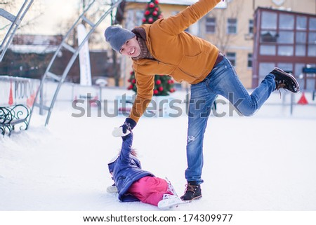 Father with his daughter skates on ice skating in the winter.