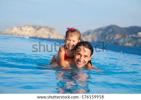 Father  with his daughter swimming in  pool at resort - stock photo