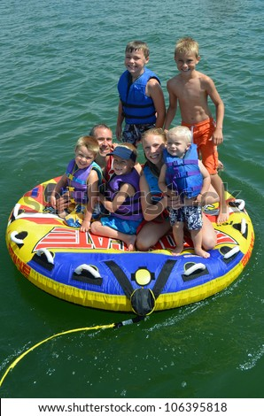 father with his kids on a tube on a lake - stock photo