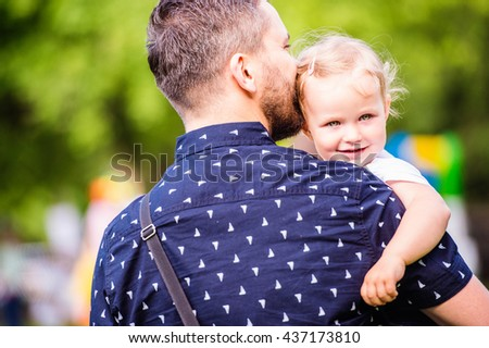 Father with his little daughter outside in park - stock photo