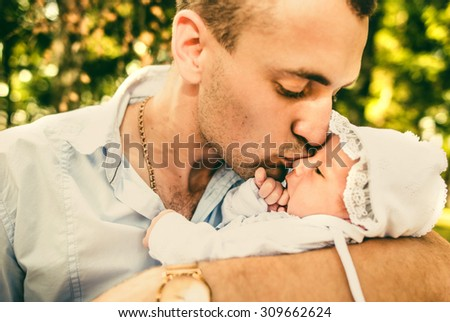 Father with his newborn baby outdoor in the park - stock photo