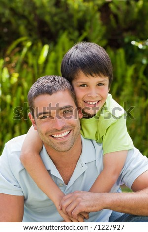 Father with his son hugging in the garden - stock photo