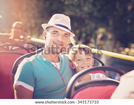 Father with his son traveling by tour bus - stock photo