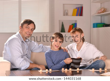 father with his sons playing lotto at home