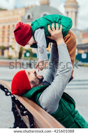 Father with his toddler son having fun in the city wearing in the same clothes. Family look. - stock photo
