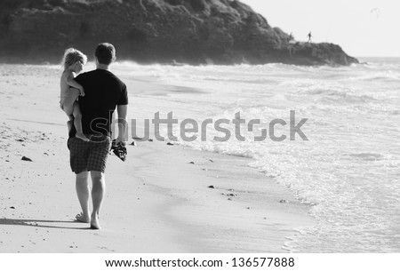 father with kid on the beach - stock photo