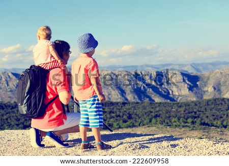 father with kids looking at scenic view in mountains
