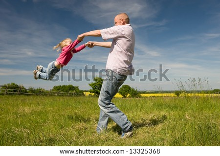 Father with little daughter playing in a meadow - stock photo