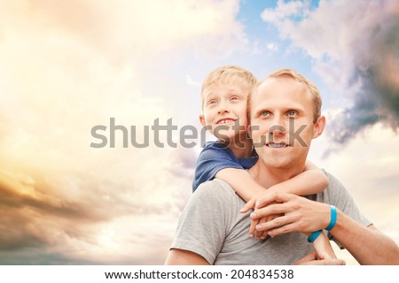 Father with little son portrait on the ky background - stock photo