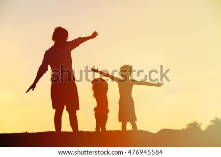 father with son and daughter silhouettes play at sunset